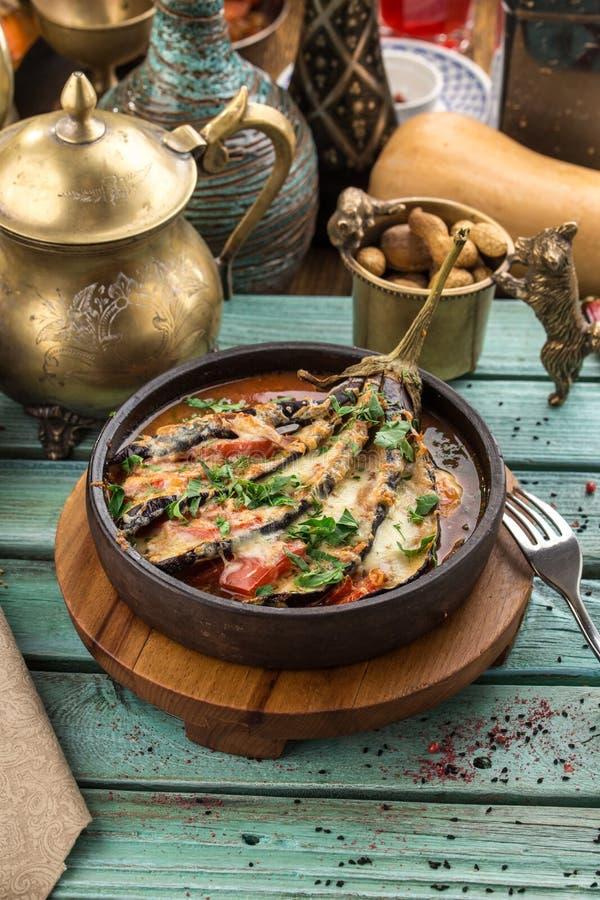 De gebakken aubergine vulde met vlees, tomaten, paprika, ui en kaas op blauwe houten lijst royalty-vrije stock foto