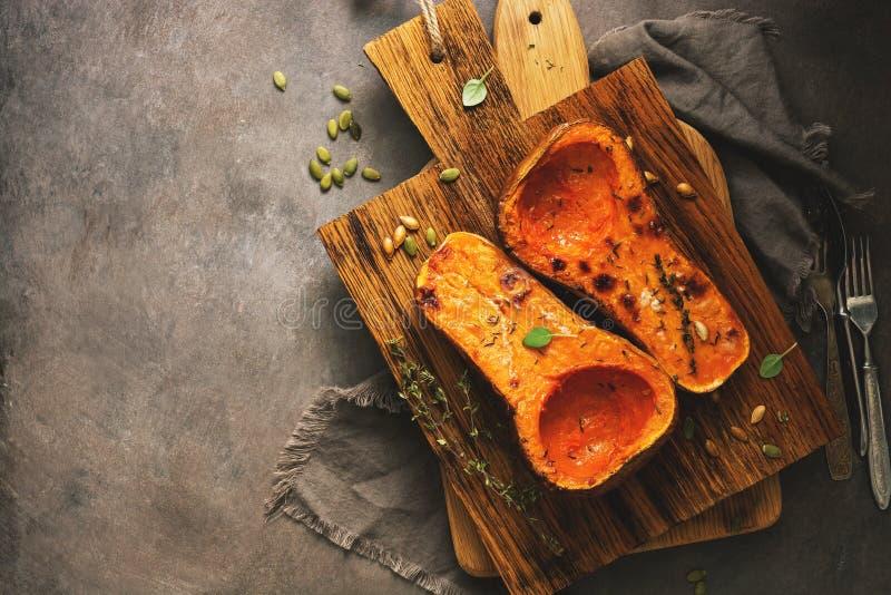De gebakken pompoen of butternut de pompoen met kruiden op een knipselraad, donkere rustieke achtergrond, vlakte legt, hoogste me stock afbeelding