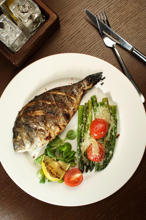 De gebakken vis met verschillende groenten is basis van een natuurlijke voeding stock foto's