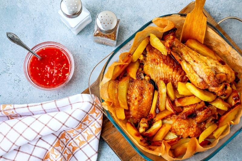 De gebakken vleugels van Turkije met aardappelstukken in een vierkante bakselschotel op een grijze keukenlijst met saus en kruide royalty-vrije stock foto's