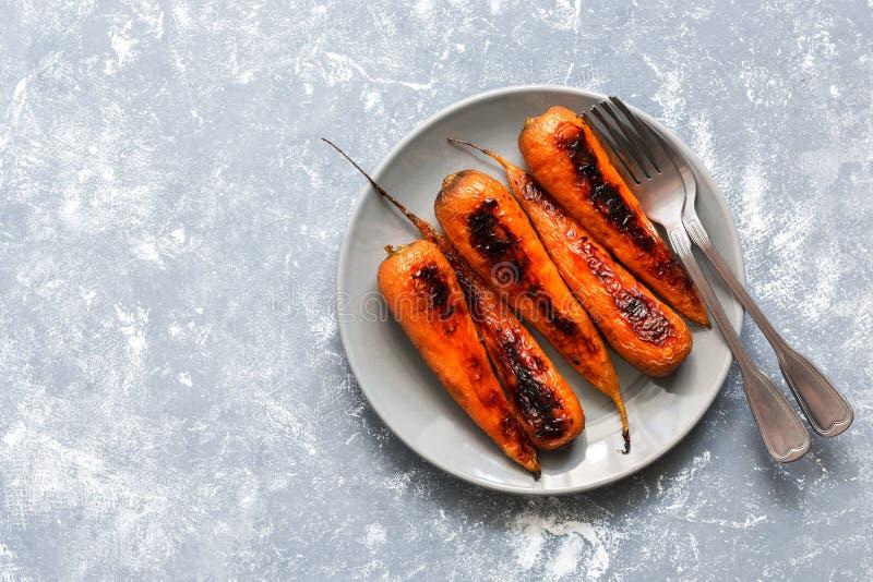 De gebakken wortelen worden gediend op een grijze plaat Vegetarisch voedsel Vlak leg van de exemplaarruimte royalty-vrije stock fotografie
