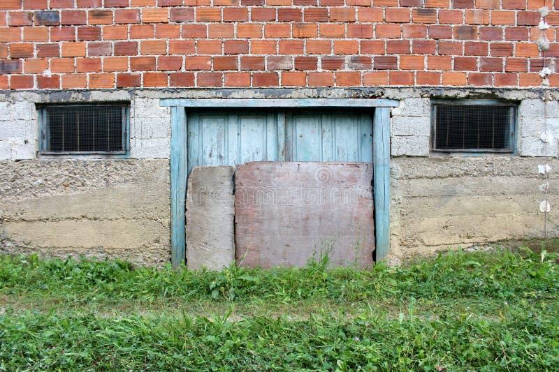 De gebarsten houten kelderverdiepingsdeuren met toegevoegde raad als bescherming tegen zware regen zetten op concrete muur met tw stock afbeeldingen