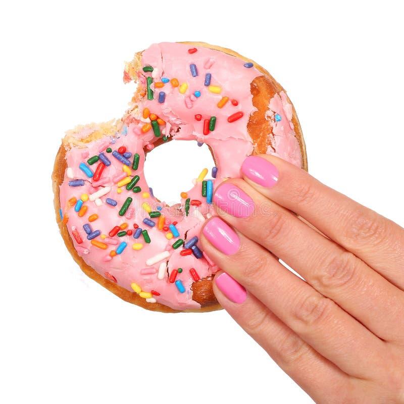 De gebeten Doughnut met bestrooit in geïsoleerde Vrouwenhand stock foto