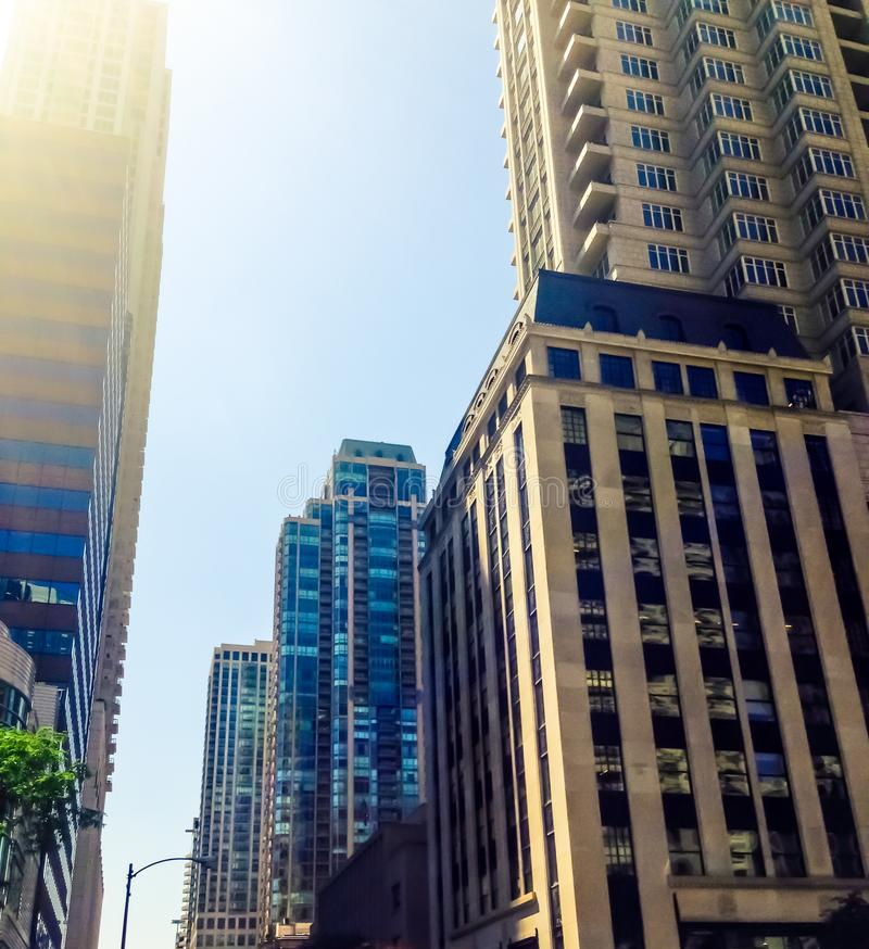 De gebouwen die van de binnenstad van Chicago omhoog tonend verscheidene prominente gebouwen onder een blauwe hemel kijken royalty-vrije stock afbeelding