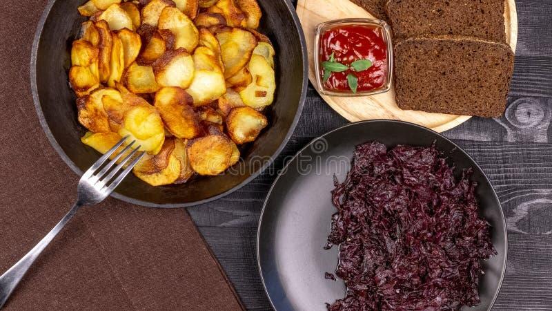De gebraden chips in een pot met donkere rogge paneren op een houten plaat en een eigengemaakte gestoofde kool, op een zwarte pla stock foto's