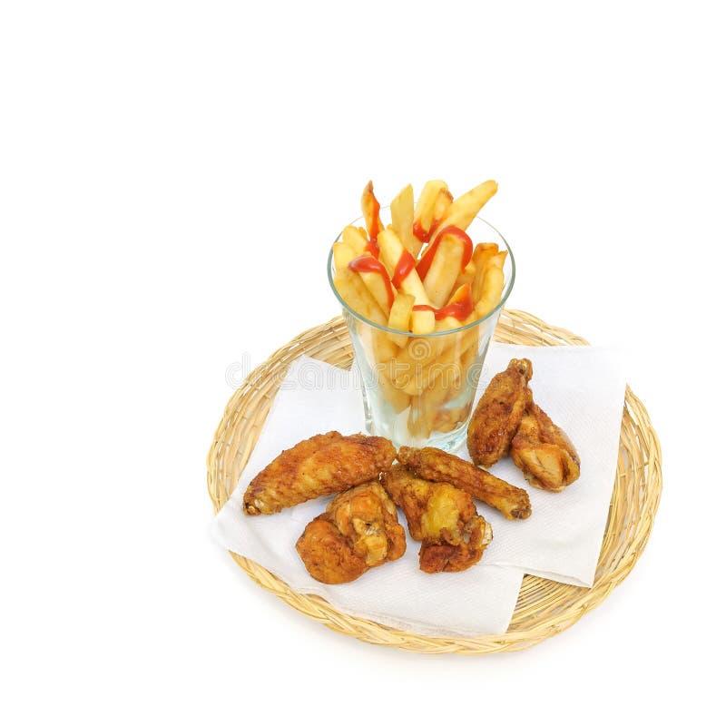 De gebraden die aardappel als frieten in een glas wordt gesneden en braadde kippentrommelstokken en vleugels op een document serv royalty-vrije stock afbeelding