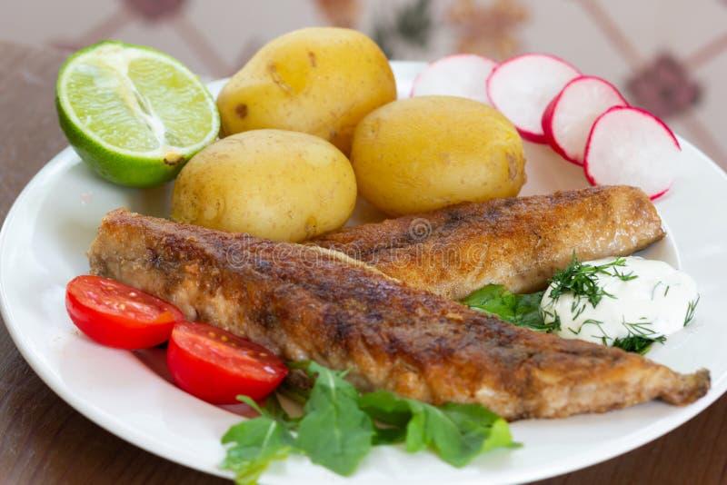 De gebraden die makreel met aardappel met huid wordt gekookt en de groenten en de kalk versieren met witte saus stock afbeeldingen
