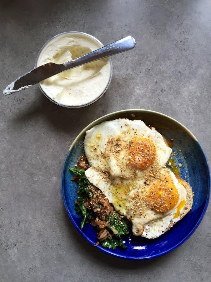 De gebraden eieren boven op van sautéed boerenkool en uien: eigengemaakt ontbijt royalty-vrije stock foto