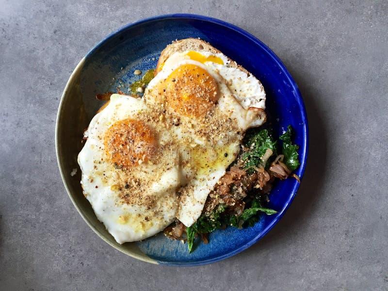 De gebraden eieren boven op van sautéed boerenkool en uien: eigengemaakt ontbijt stock foto's