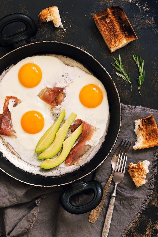 De gebraden eieren met bacon worden gediend in een pan met avocado Een heerlijk hartelijk ontbijt in een rustieke stijl op een do stock afbeeldingen