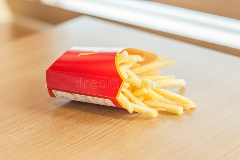 De gebraden gerechten van de McDonald` s aardappel op houten lijst stock afbeelding