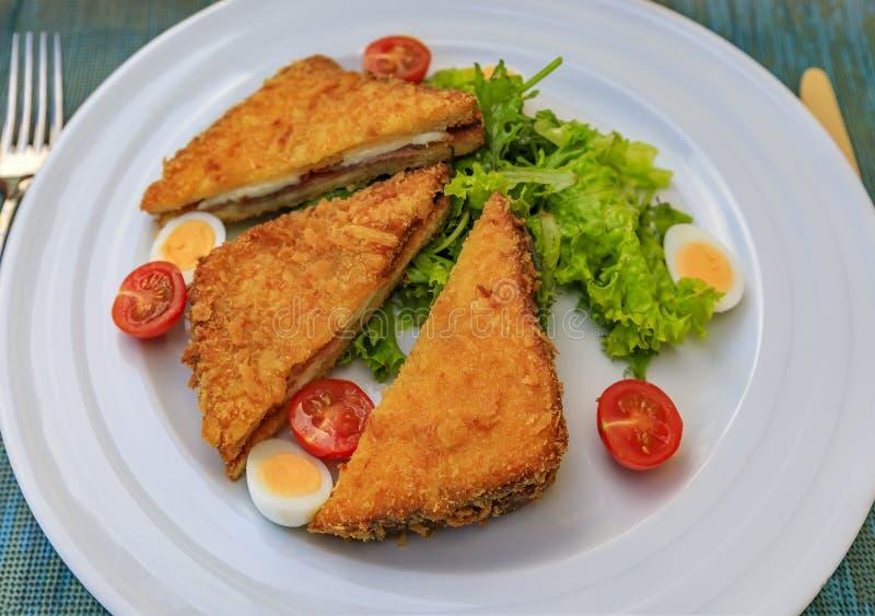 De gebraden sandwich van Montenegro, fritter, met geitkaas en het vlees van Njeguski prsut met tomaten, kookte kwartelsei en sala royalty-vrije stock afbeeldingen