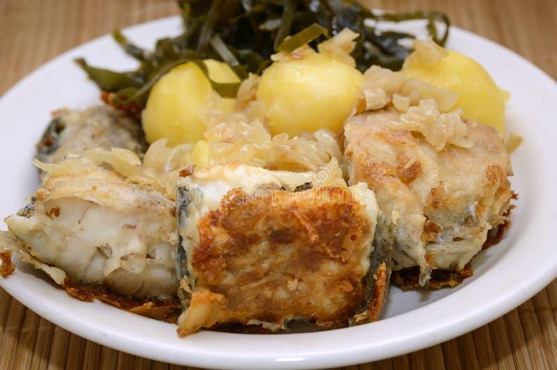 De gebraden vis, de gekookte aardappels en de zeekool liggen op een plaat op een bamboeservet Close-up, selectieve nadruk stock afbeeldingen