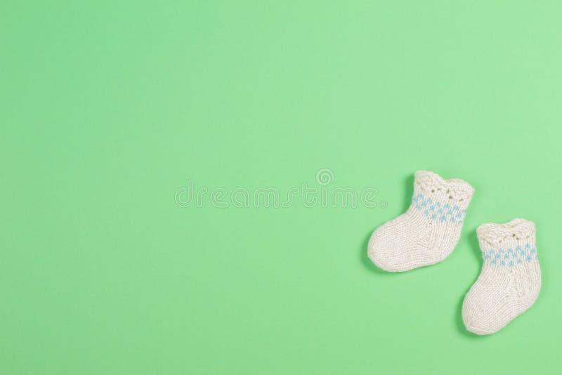 De gebreide sokken van de babywol op groene achtergrond royalty-vrije stock fotografie
