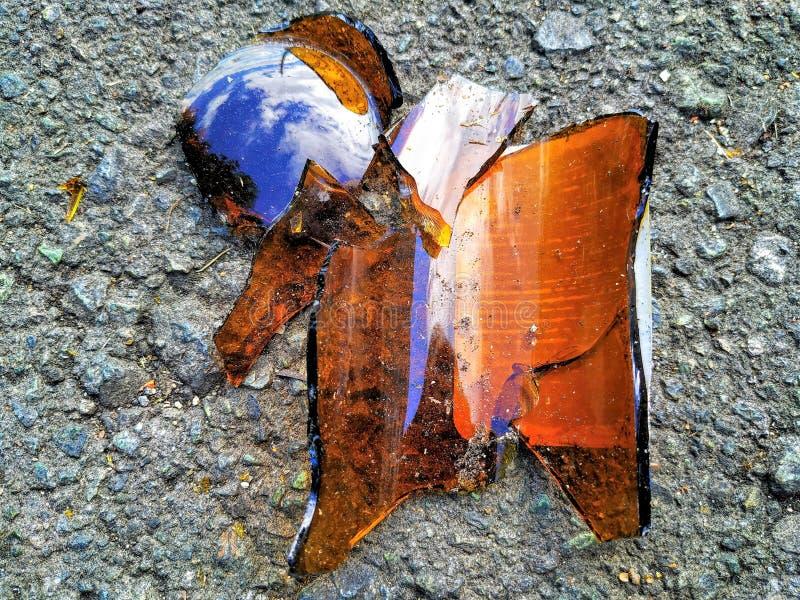 De gebroken bruine leugens van de glasfles op het grijze asfalt stock afbeelding