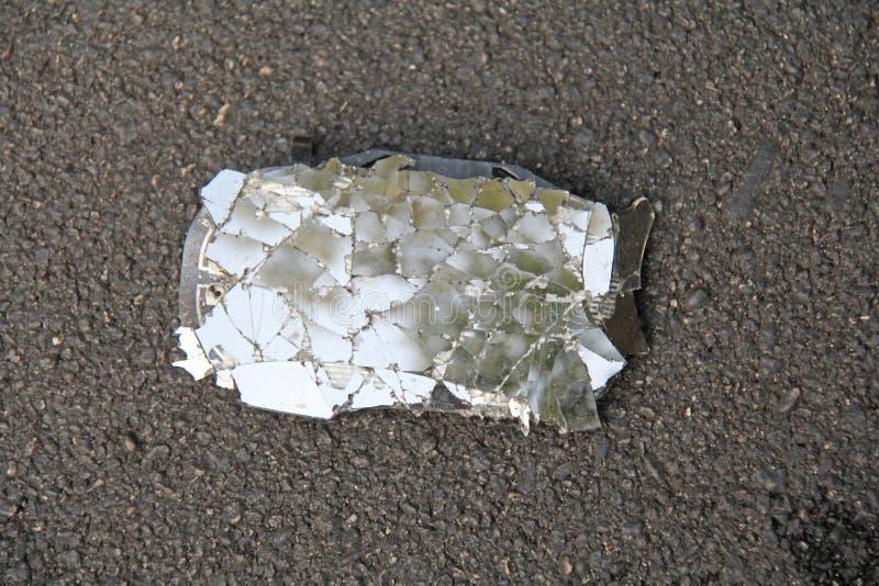 De gebroken en Gebarsten Auto of Motorfietsspiegel ligt op de Weg Ongeval op de weg Het veilige Drijven van Vervoer, Regels van W royalty-vrije stock afbeelding