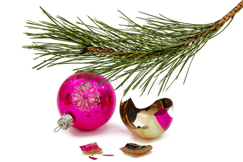 De gebroken Kerstmisbal ligt onder geïsoleerde tak van de pijnboom, stock afbeeldingen