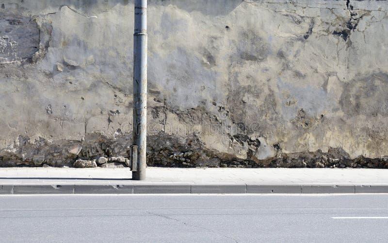 De gebroken muur dichtbij aan weg stock foto's
