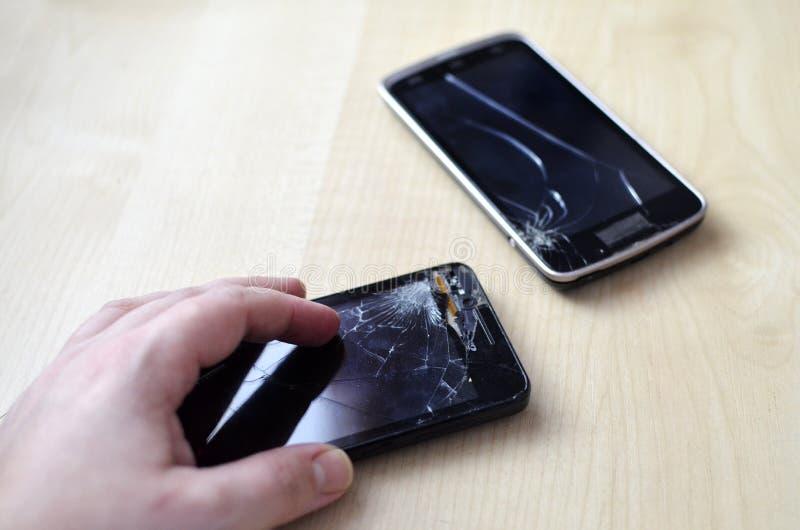 De gebroken telefoon van de het schermcel op grijze achtergrond Smartphone-Verzekering en het Mobiele concept van de telefoongara stock afbeeldingen