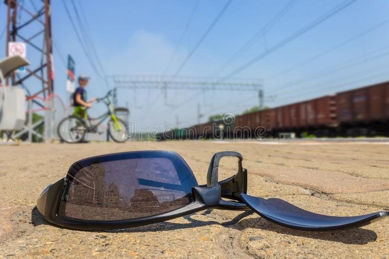 De gebroken zonnebril ligt in het station amid een voorbijgaande jongen stock afbeelding