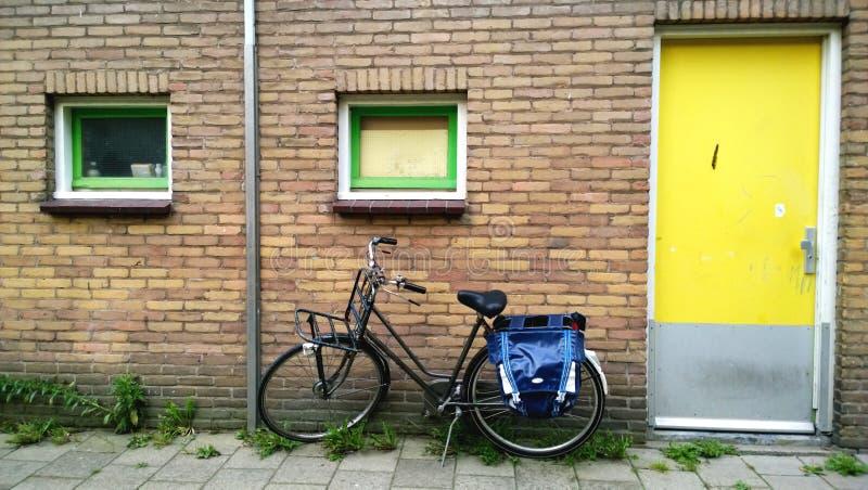 De gebruikelijke ingang van Amsterdam in een woonhuis, dichtbij een geparkeerde fiets Heldere gele voordeur stock fotografie