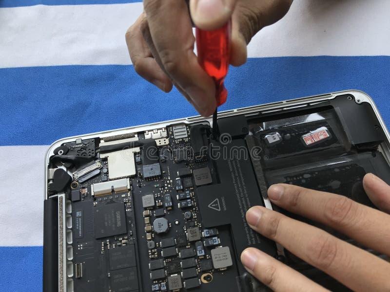 De gebruiker van Apple Mac-boeklaptop toont hoe te om batterij te veranderen royalty-vrije stock foto