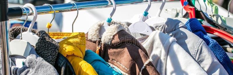 De gebruikte die kleren, de jasjes en de lagen van de babywinter op rek worden getoond royalty-vrije stock foto