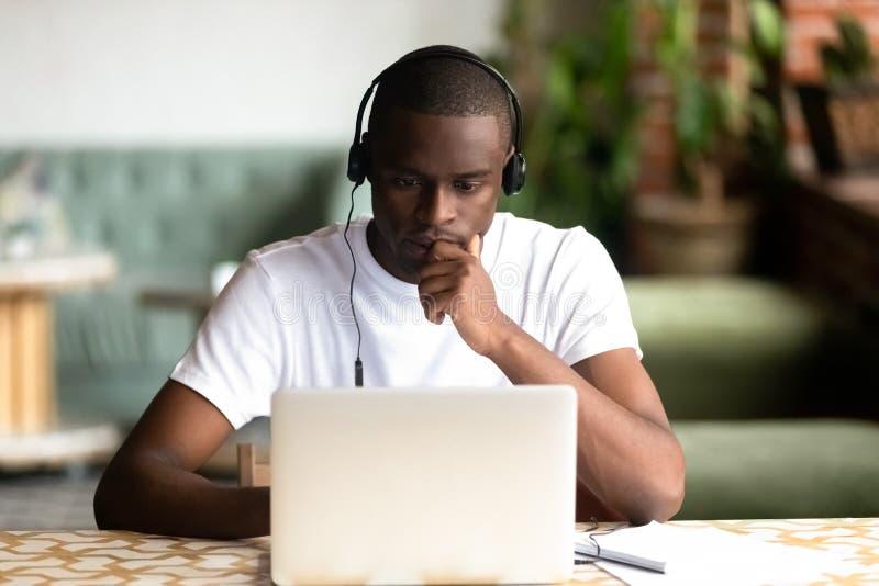 De geconcentreerde Afrikaanse Amerikaanse hoofdtelefoons van de mensenslijtage, die laptop met behulp van stock foto's