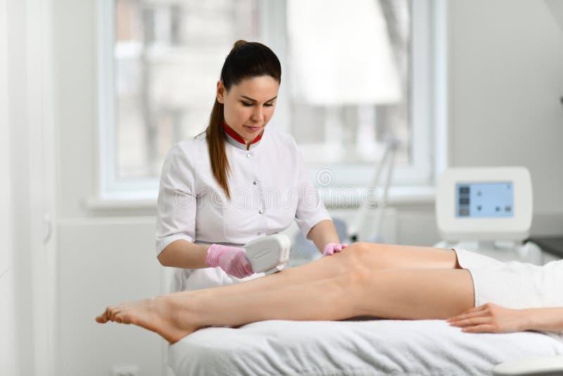 De geconcentreerde artsenschoonheidsspecialist voert een kosmetische procedure aangaande de benen van de patiënt met elektronisch stock foto's