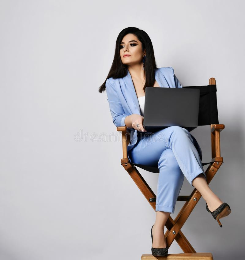 De geconcentreerde bedrijfsvrouw in blauwe formele slijtagezitting met laptop op hoge leunstoel en bekijkt iets aan de kant van h stock foto's