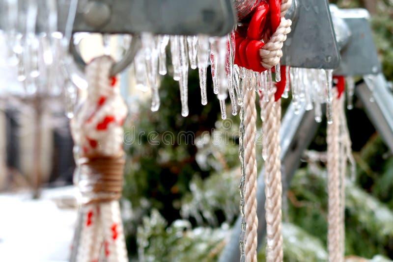 De geconcentreerde bevroren kabel hangt voor schommeling voor kinderen in de winter stock fotografie