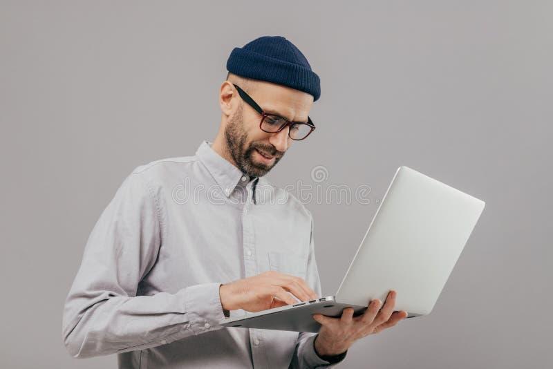 De geconcentreerde gebaarde mannelijke administratieve arbeiderscoördinaten werken aan afstand, zoekt informatie over laptop comp royalty-vrije stock foto's