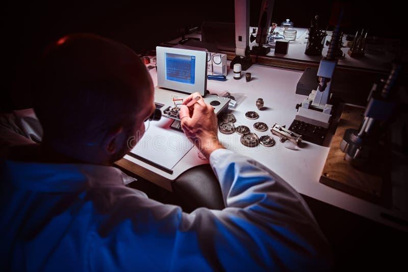 De geconcentreerde horlogemaker werkt bij zijn eigen studio stock fotografie