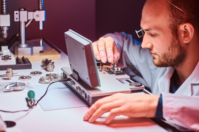 De geconcentreerde horlogemaker werkt bij zijn eigen studio stock foto's
