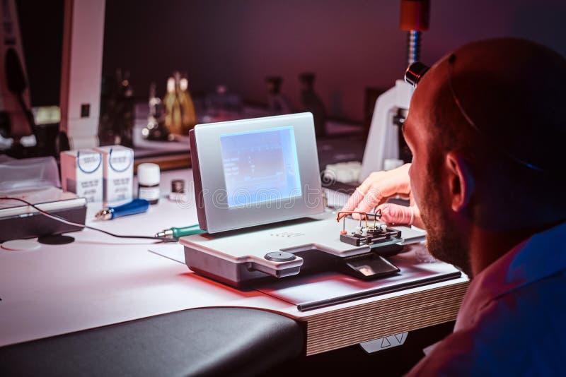 De geconcentreerde horlogemaker werkt bij zijn eigen studio stock afbeeldingen