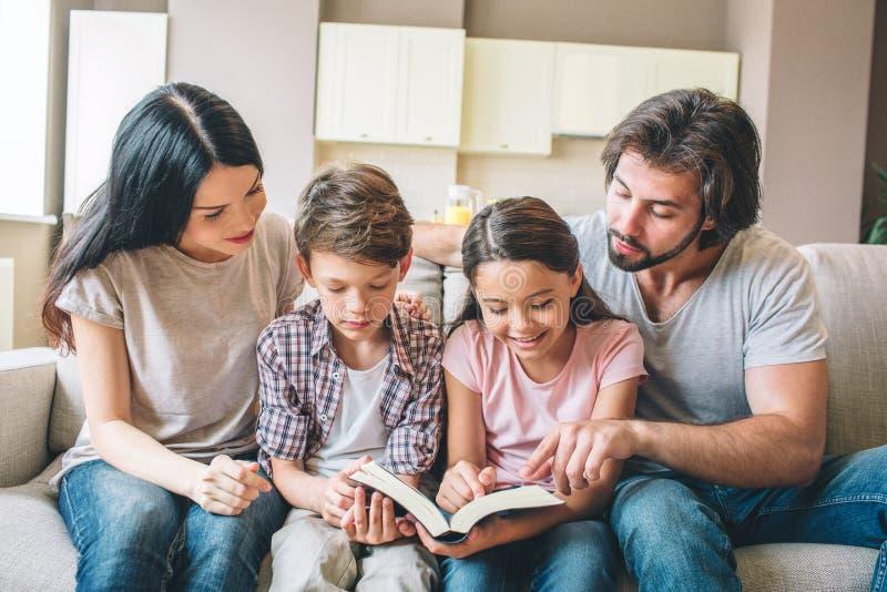 De geconcentreerde jonge geitjes zitten op bank met hun ouders en lezen een boek De kinderen houden samen het De kerel richt stock afbeeldingen
