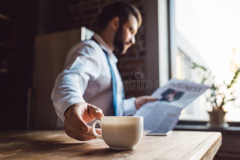 de geconcentreerde krant van de zakenmanlezing op keuken in ochtend terwijl het hebben van kop royalty-vrije stock afbeelding