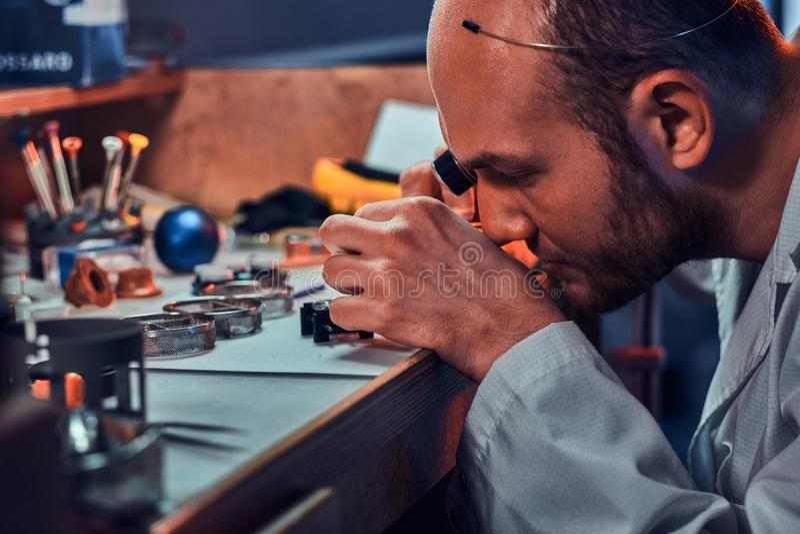 De geconcentreerde meester werkt aan het horloge van de cli?nt op zijn workshop stock foto