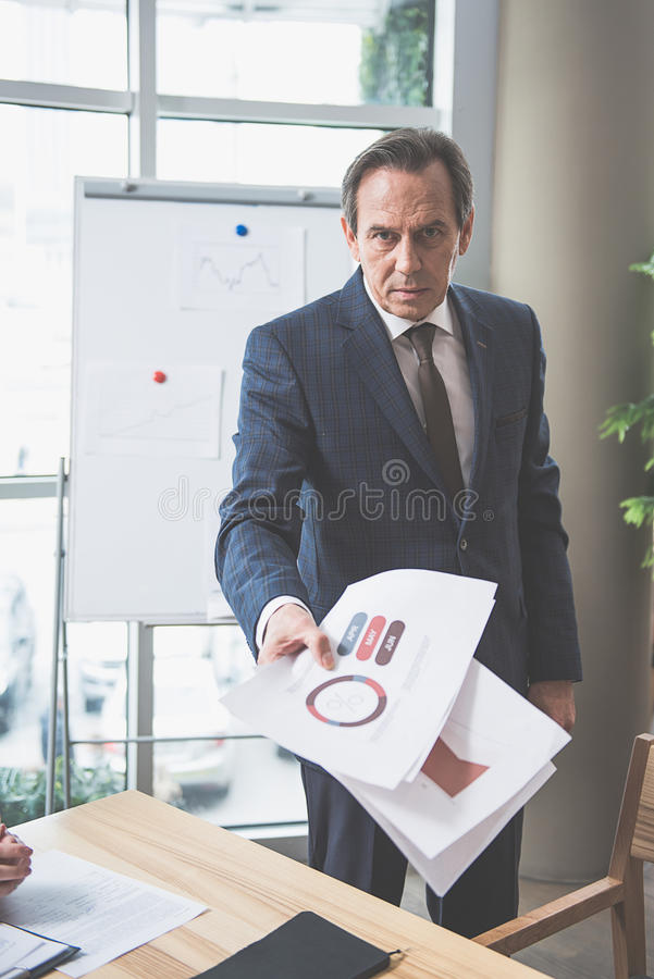 De geconcentreerde mens houdt documenten stock afbeelding