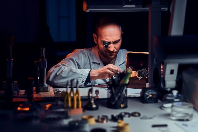 De geconcentreerde mens werkt bij zijn workshop met monocle en andere hulpmiddelen herstellend oude horloges stock afbeelding