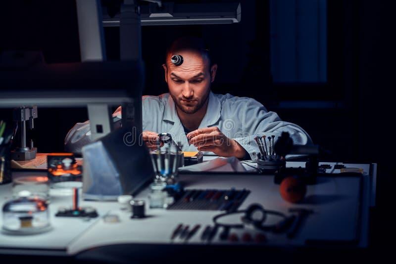 De geconcentreerde mens werkt bij zijn workshop met monocle en andere hulpmiddelen herstellend oude horloges stock foto's
