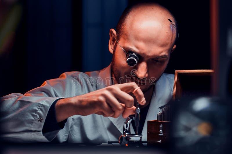 De geconcentreerde mens werkt bij zijn workshop met monocle en andere hulpmiddelen herstellend oude horloges stock foto