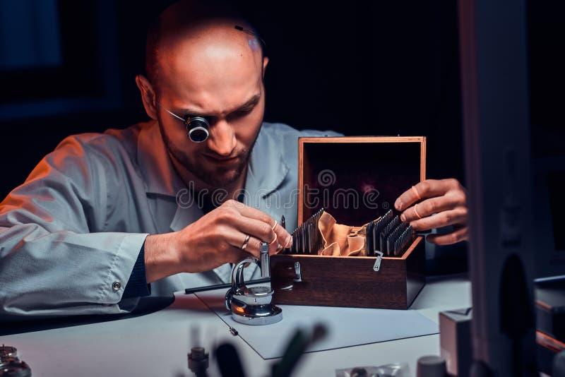 De geconcentreerde mens werkt bij zijn workshop met monocle en andere hulpmiddelen herstellend oude horloges royalty-vrije stock afbeeldingen