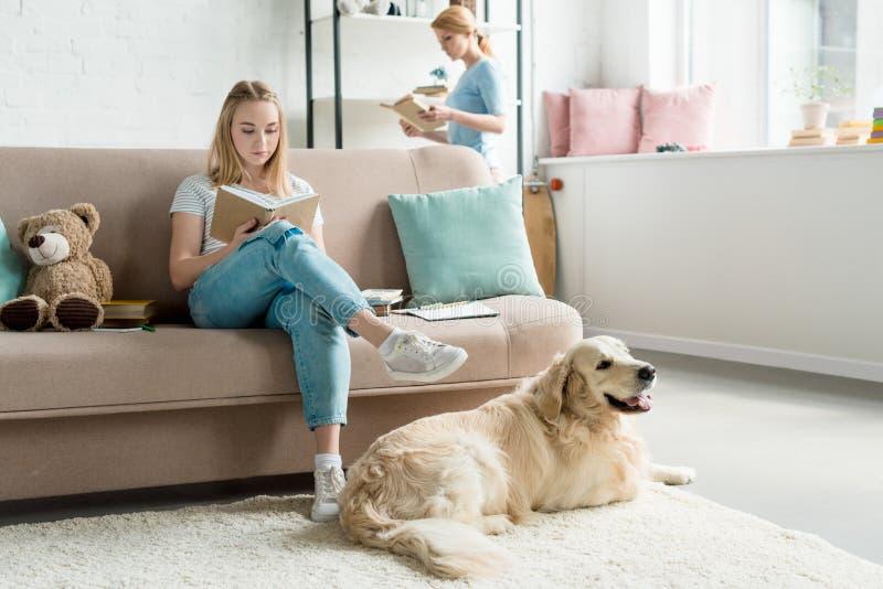 de geconcentreerde moeder en tienerdochterlezing boekt samen royalty-vrije stock afbeelding