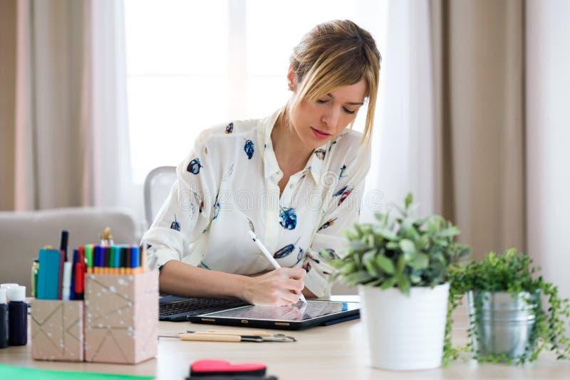 De geconcentreerde mooie jonge tekening van de ontwerpervrouw iets op haar digitale tablet op het kantoor royalty-vrije stock foto's
