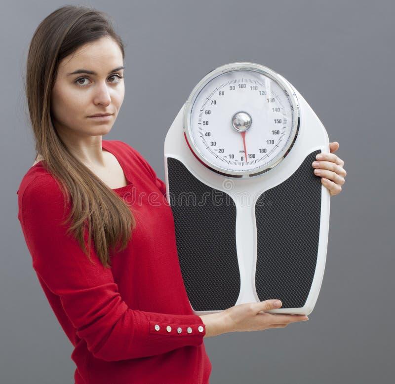 De geconcentreerde slimme 20 schalen van de meisjesholding voor het controleren van gewichtsverlies royalty-vrije stock fotografie