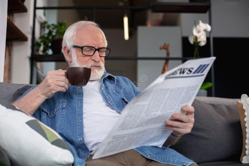De geconcentreerde teruggetrokken krant van de mensenlezing met koffie stock foto's