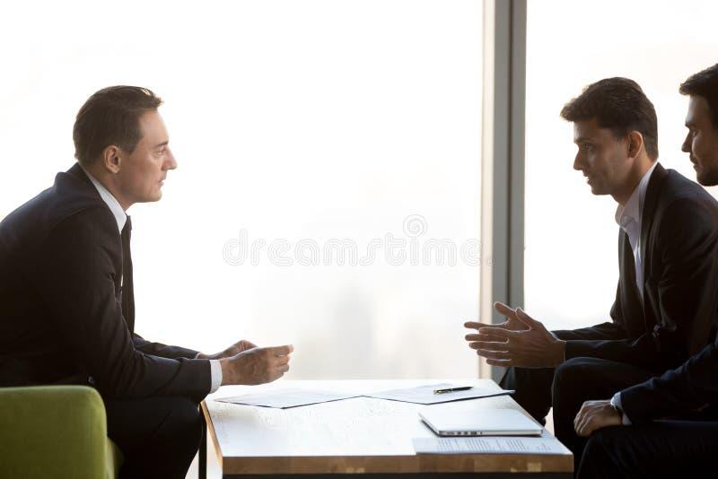 De geconcentreerde zakenlieden onderhandelen op vergadering die samenwerking bespreken royalty-vrije stock foto's