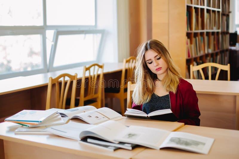 De geconcentreerde zitting van de studentenvrouw bij bureau in oude universitaire bibliotheek die boeken bestuderen en voor exame stock fotografie