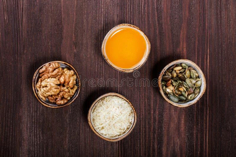 De gedeeltekoppen gezonde zoete ingrediënten op donkere houten lijst, gebraden pompoenzaden, raspten parmezaanse kaaskaas, honing royalty-vrije stock fotografie